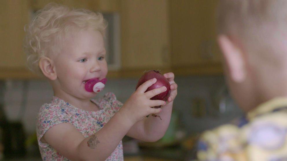 Barn med napp håller i rödlök.