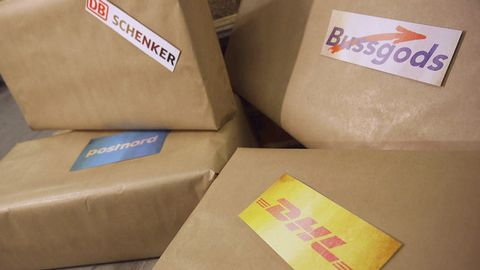 Fyra bruna paket med företagsloggor från olika frakbolag.