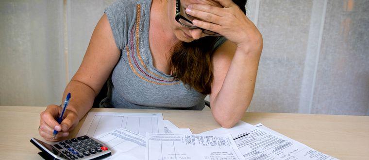 Kvinna sitter vid ett bord med mängder av räkningar.