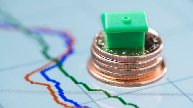 Ett grönt litet Monopolhus på en stapel av kronor