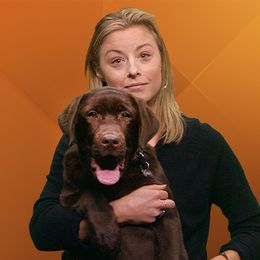 Blond kvinna med hund i famnen.