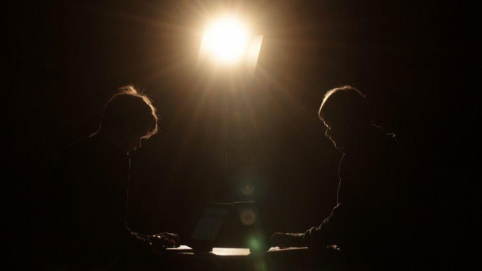Två män sitter vid datorer.