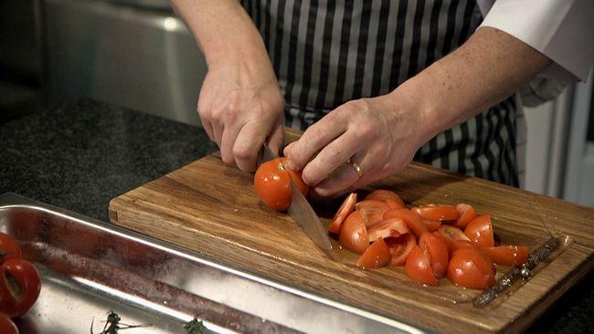 En man hackar tomat med kockkniv