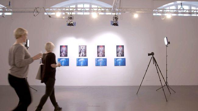 Karin och Paulina ser tavlorna på väggen i galleri