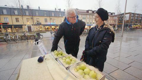 Man och kvinna i stadsmiljö, vid ett bord med äpplen.