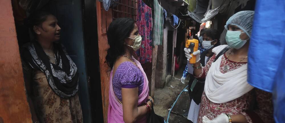 Sjukvårdspersonal screenar invånare i slumområdet Dharavi i Bombay, ett av de största slumområdena i Asien.