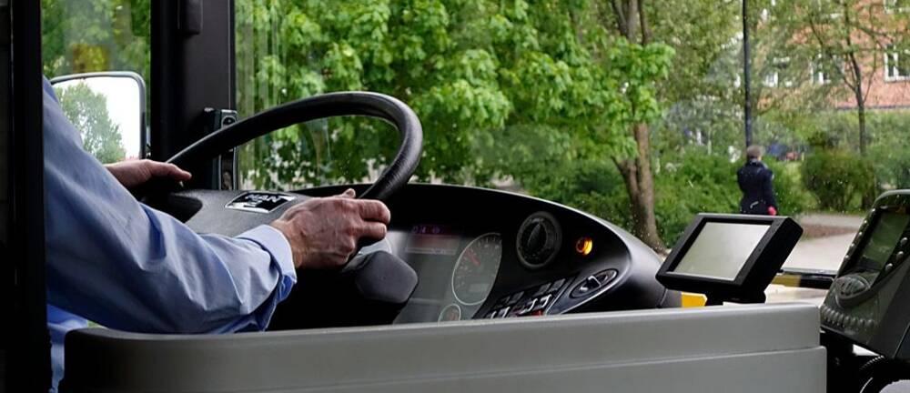 En bild på en busschaufför som kör en buss. Man ser att han håller i ratten och skog utanför fönstret.