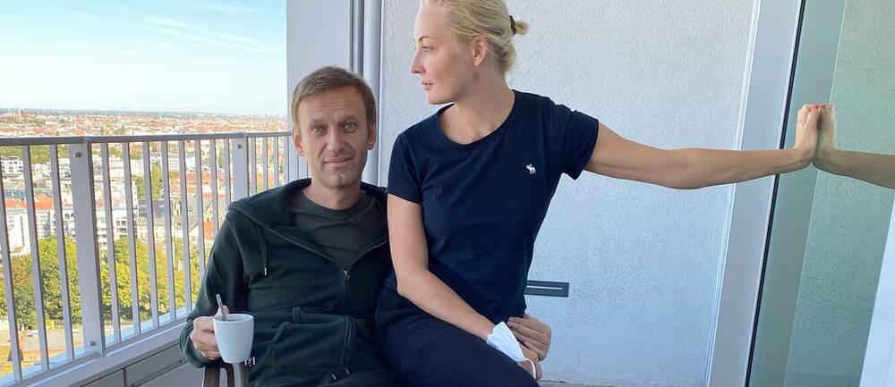 Aleksej Navalnyj med en kaffekopp i handen tillsammans med frun Yulia på en balkong.