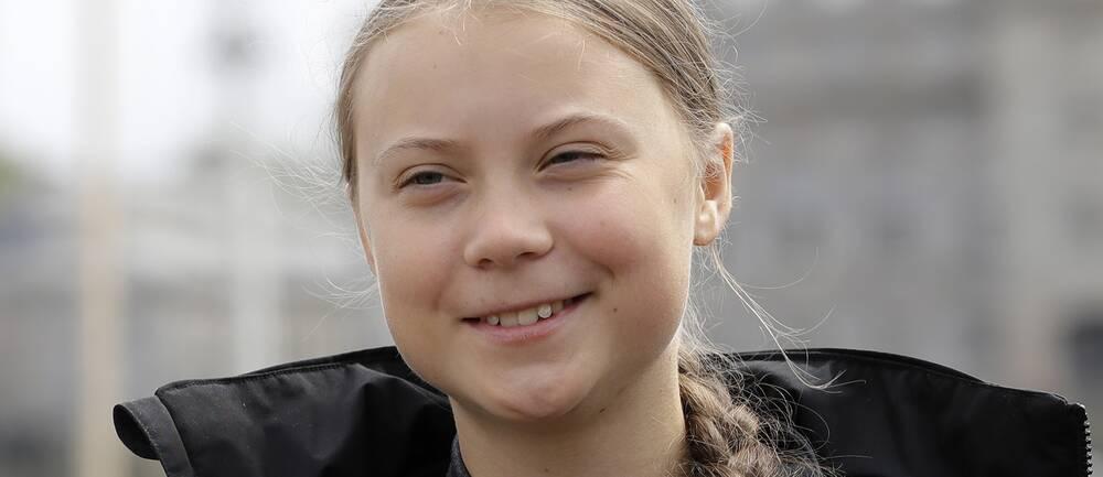 Greta Thunberg i svart jacka och fläta, ler mot kameran.