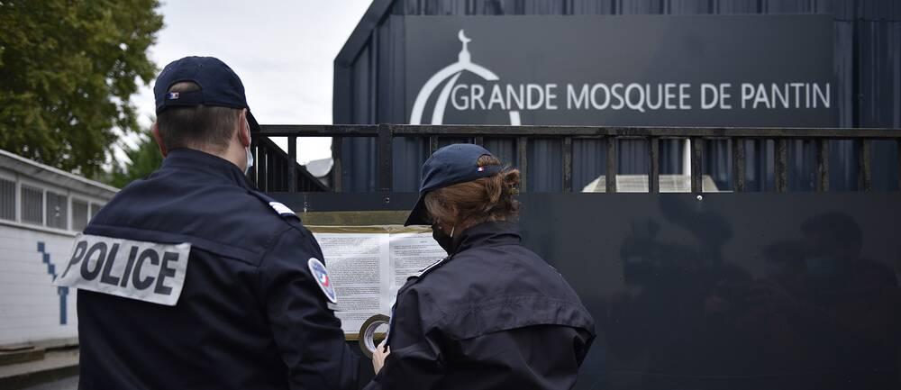 Fransk polis sätter upp myndighetsbeslut utanför moskén i förorten Pantin under tisdagen.