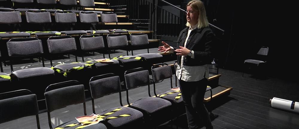 Linda Stenberg, teaterchef på Byteatern i Kalmar står med händerna framför sig och visar hur Byteatern har coronasäkrat sina sittplatser. Linda Stenberg står framför gradängen med svarta stolsrader. En del av stolarna har gul och svart avspärringstejp på sig.