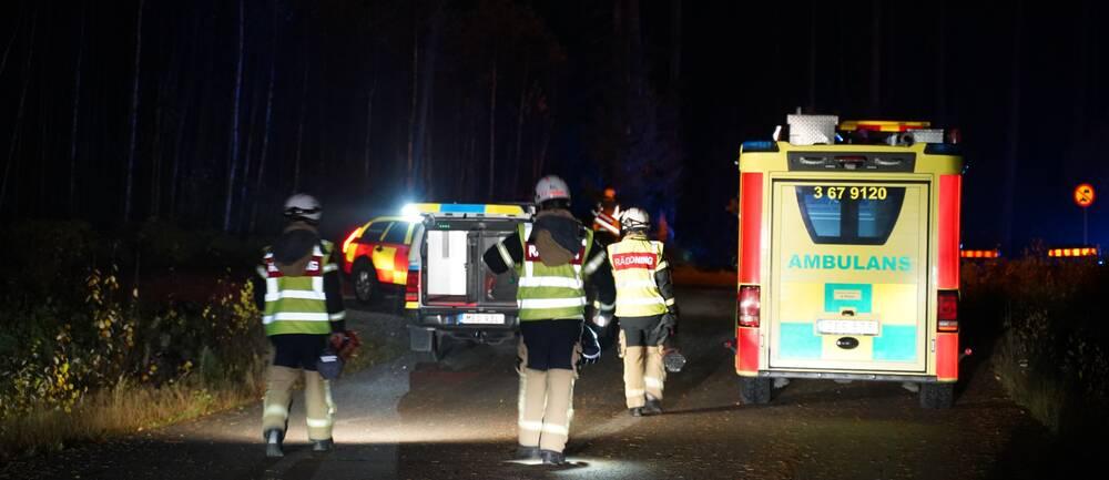 Det är natt och räddningstjänst, polis och ambulans befinner sig i en skog. Björkar skymtas i bakgrunden. I mitten av bilden ser man ryggarna på tre brandmän från räddningstjänsten. I bakgrynden skymtas en polisbil samt en bil från räddningstjänsten. Till vänster i bild står en ambulans.