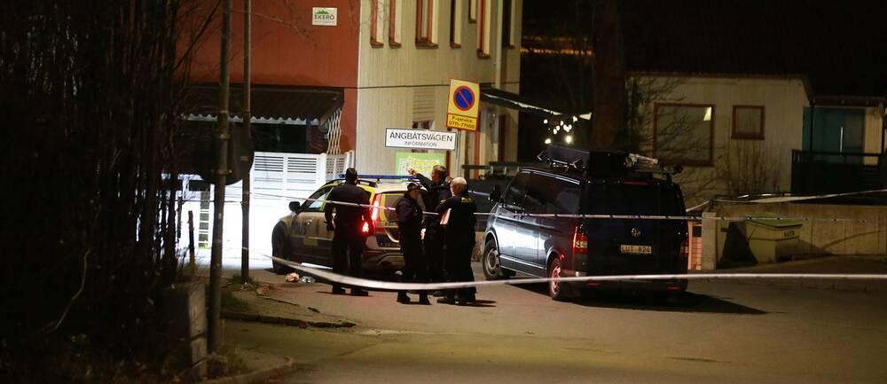 Poliser står samlade vid ett par polisbilar intill ett hus. Området är avspärrat.