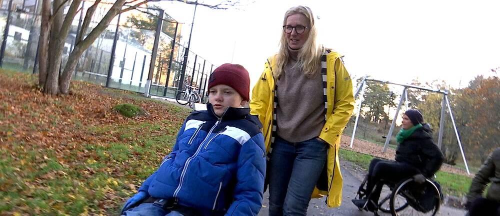 Mamma Anna går bakom Leo som kör rullstol.