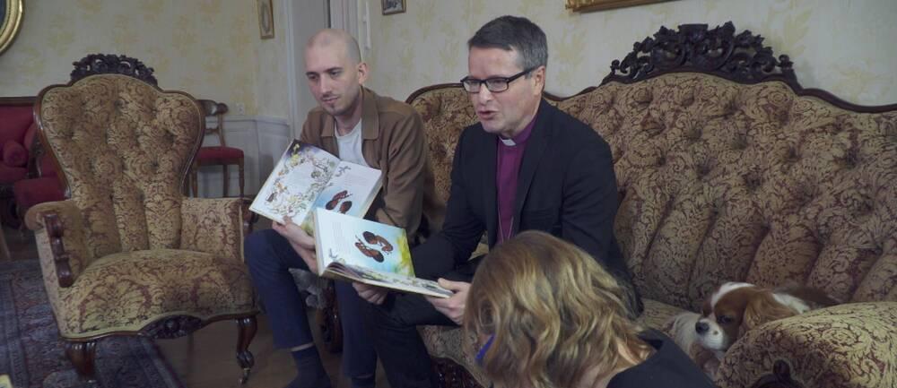 Illustratören Marcus-Gunnar Pettersson och författaren, biskop Sören Dalevi, läser ur den nya barnbibeln sittande i en soffa.