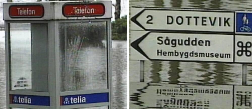 En telefonkiosk till hälften täckt av vatten samt en vägskylt som pekar mot Dottevik och Sågudden, också den med vatten en bra bit upp.