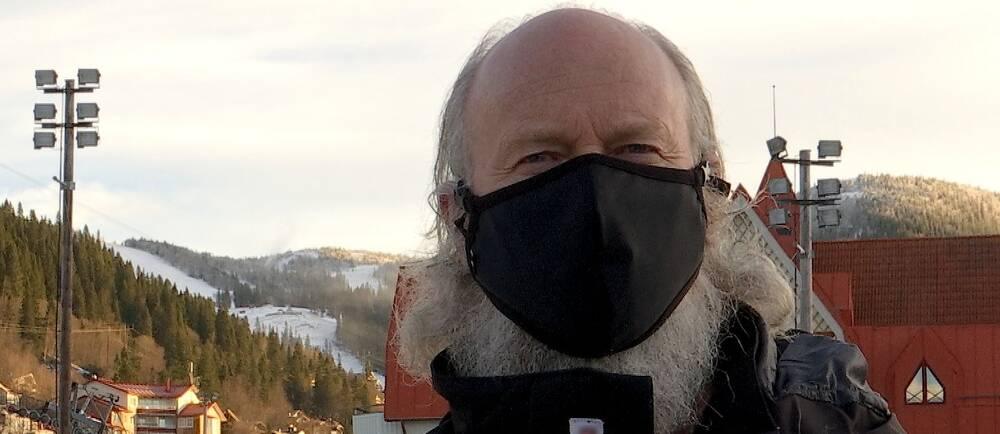 en man med munskydd, vy ner mot skidbacke och byggnader i bakgrunden