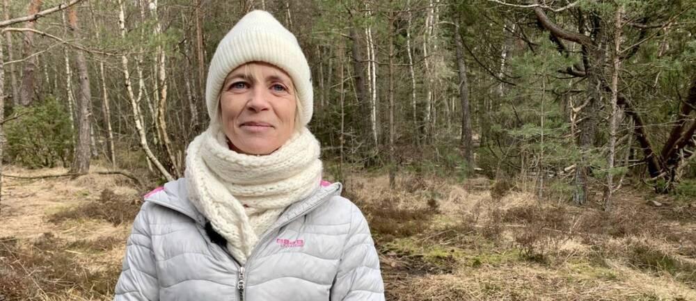 Leende vitklädd kvinna i skogsmiljö tittar in i kameran.