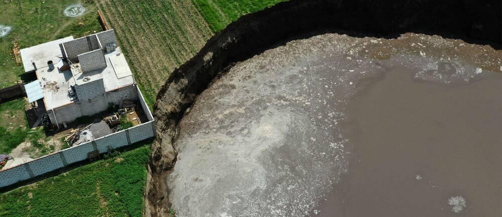Ett stort slukhål fyllt med grågrumligt vatten precis intill ett hus som ser litet ut i jämförelse.