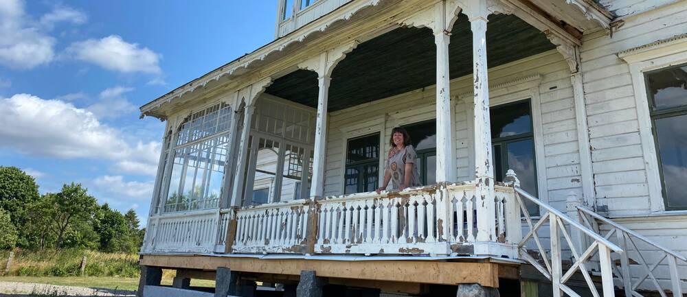 Kvinna ståendes på en sliten husveranda.
