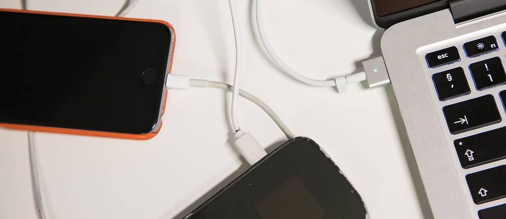 Mobiler som ligger på laddning intill en dator.