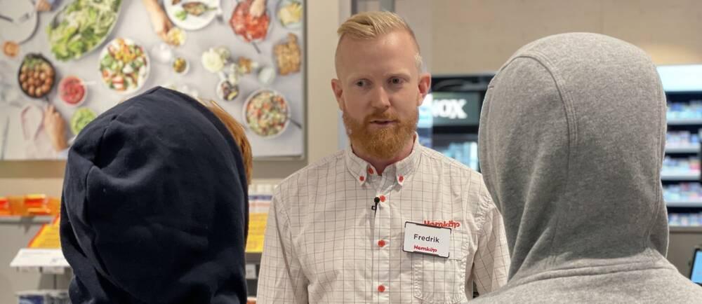 En man med skägg pratar med två ungdomar i en butik.