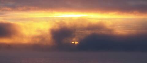 Morgonstämning över Storsjön från Ås, med Östersunds rådhustorn spirande mitt i solskivans magiska uppgång.Ännu har inte isen lagt sej och lite dimma driver långsamt fram över vattenytan mellan Östersund och Frösön.