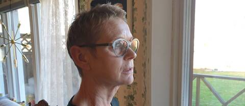 Elisabeth står vid en altandörr i sitt hem och tittar ut. Hon ser eftertänksam och allvarlig ut.