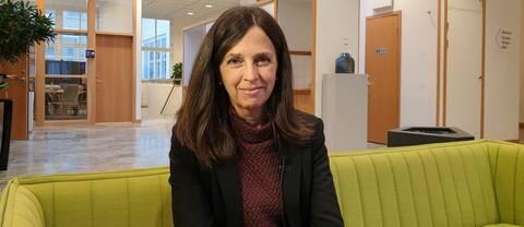 Porträttbild på Ingeborg som sitter i ett kontorslandskap.