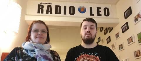 """Mia och Daniel står framför en skylt där det står """"Välkommen till Radio Leo""""."""