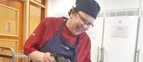 Lena står i köket, klädd i förkläde. Hon ler och häller ner grönsaker i en kastrull med vatten.