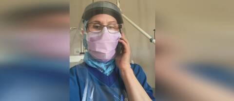 Therése står med skyddsvisir och munskydd och pratar i telefon.