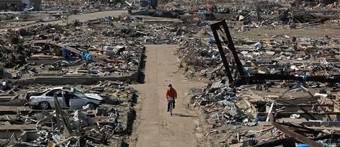 En överlevare cyklar genom ett område i Sendai som förstörts i tsunamin, den 1 april 2011.
