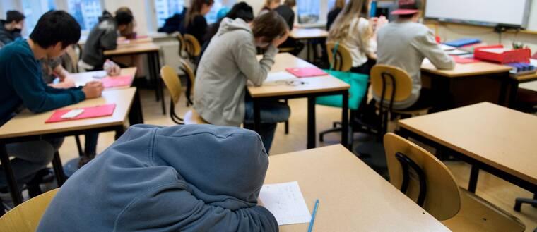 En trött högstadieelev i årskurs 8 sover med huvudet på bänken under en lektion
