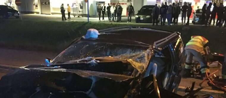 en totalkvaddad bil på en väg kvällstid, en räddningsperson arbetar, i bakgrunden vid mack står många ungdomar och tittar
