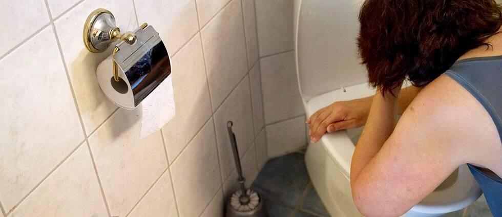 En kvinna står böjd över en toalett.