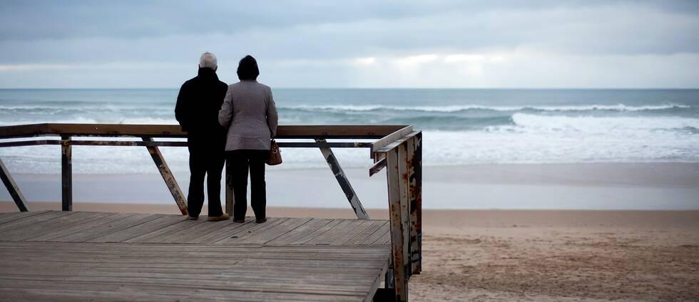 Äldre par som står på altan och blickar ut mot sandstrand och havet. Ska symbolisera pensionärer som bosatt sig i Portugal som snart kan komma att behöva betala skatt i landet.