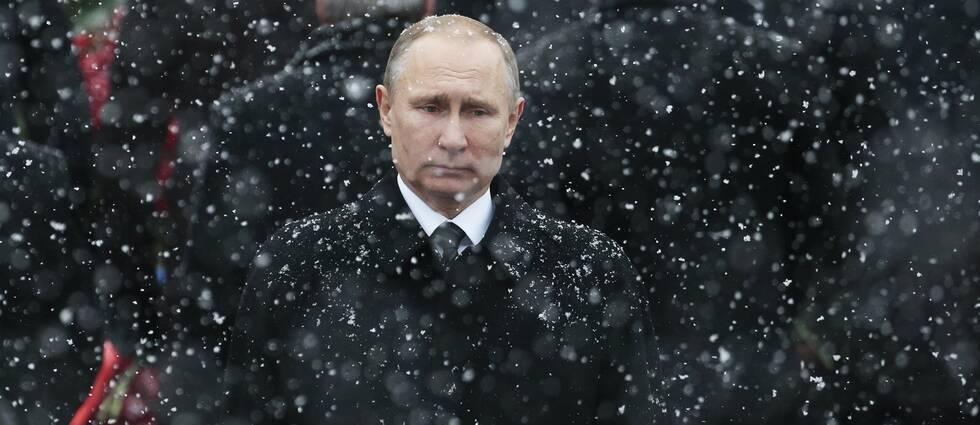 Ryska presidenten Vladimir Putin står klädd i svart i ett snöfall.