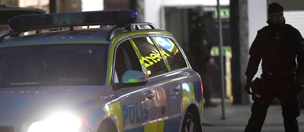 En polisman står bredvid en polisbil i mörkret.