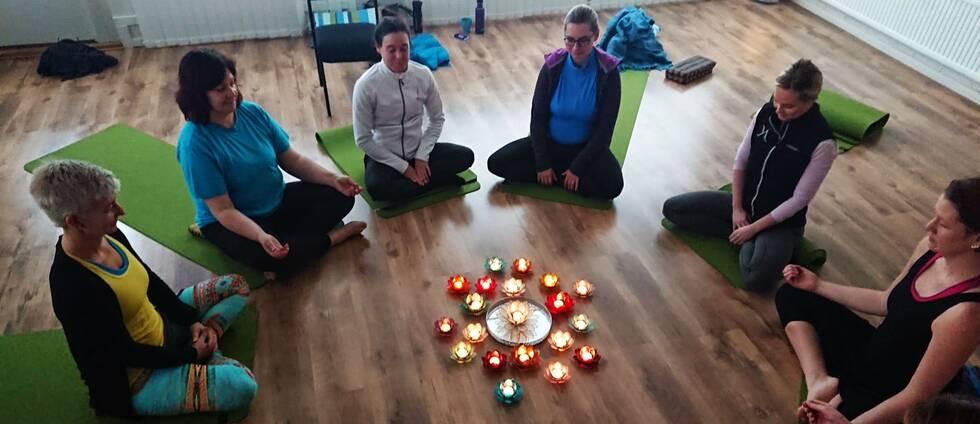 Åtta kvinnor sitter i meditationspose i en ring på golvet. I mitten står flera ljuslyktor i olika former. Lyktorna har formen av lotusblommor.