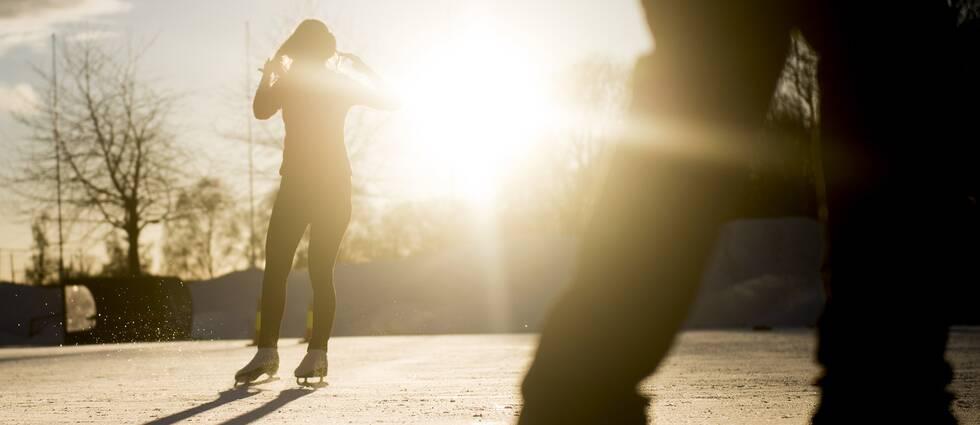 På bilden syns två människor som åker skridskor i vintersolen.
