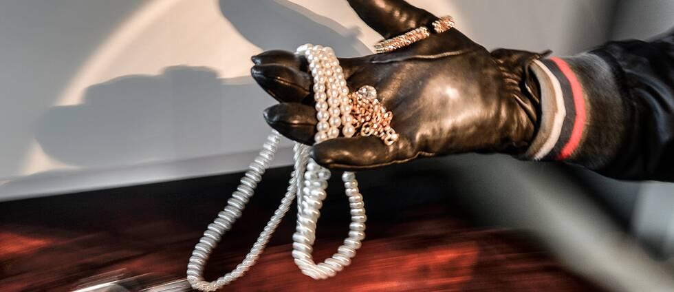 En hand med en handske stjäl smycken från en byrå