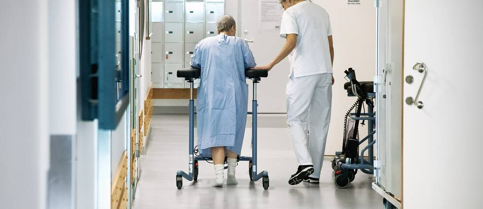 Kvinna med rullator och sjuksköterska.