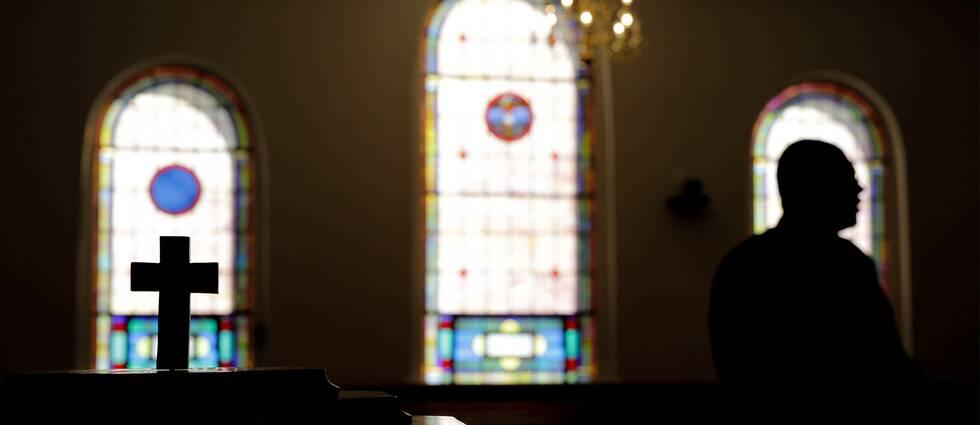 Ett kors och en präst i en kyrka.