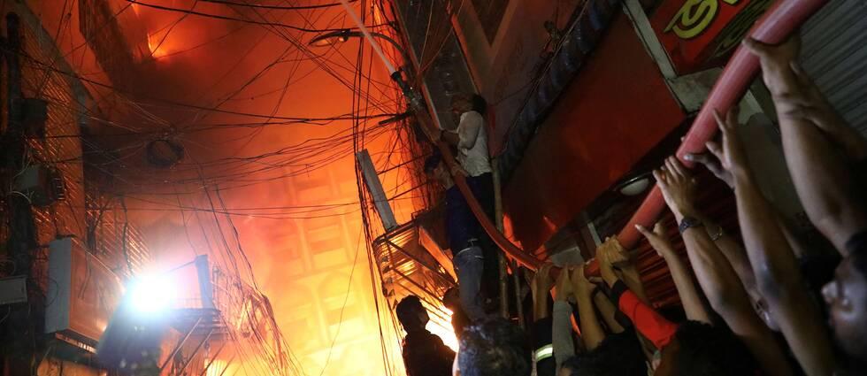 Personer hjälps åt att släcka branden som bröt ut i ett flerfamiljshus som även användes som kemiskt lager i Dhakas äldre delar.