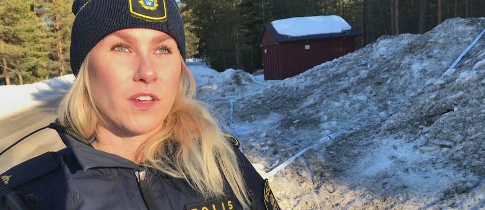 em ung kvinna i poliskläder intervjuas vid vintrig väg.