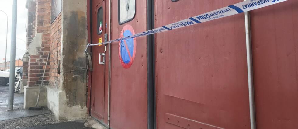 Ett polisavspärrningsband framför en dörr till en lokal i en industribyggnad.