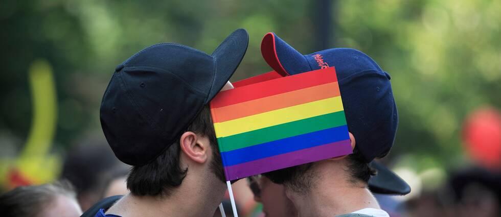 Två män kysser varandra bakom en regnbågsflagga.