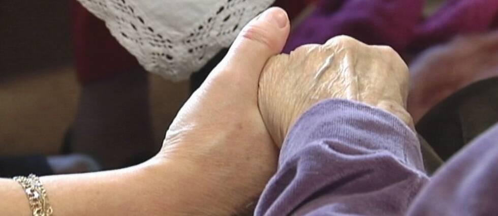 Närbild på en äldre människas hand som hålls av en yngre hand.