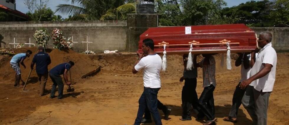 Fem män bär på en kista. I bakgrunden syns tre män som gräver med spadar.